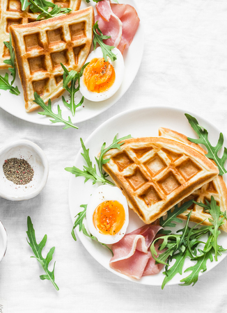 Savory waffles, boiled egg, ham and arugula on light background, top view. Appetizers, snack, brunch. Delicious healthy food concept. Flat lay