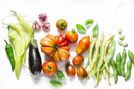 Vegetables background. Tomatoes, green beans, pepper, eggplant, garlic on a light background, top view. Flat lay, copy space