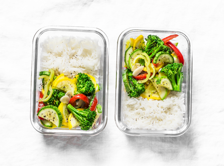 Vegetarian lunch box - stewed vegetables and rice on a light background, top view. Health food concept