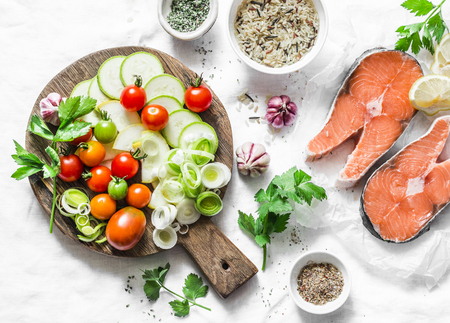 Ingredients for  healthy, balanced lunch - salmon and vegetables. Red fish, zucchini, squash, cherry tomatoes, leek, wild rice, spices on a light background, top view. Flat lay Banque d'images