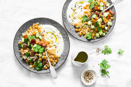 Couscous, chickpeas, vegetables salad with Greek yogurt on a light background. top view. Healthy food concept 免版税图像