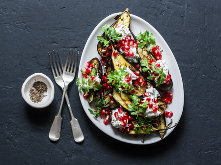 Baked eggplant with feta, greek yogurt, cilantro sauce and pomegranate seeds on dark background, top view. Delicious snack, tapas, appetizers Imagens