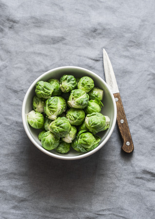 Fresh brussels sprouts in white bowl on grey background, top view