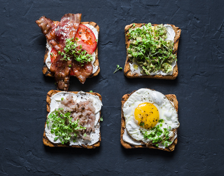 Choice of sandwiches for breakfast, snack, appetizers - avocado puree, fried egg, tomatoes, bacon, cream cheese, smoked mackerel grilled whole grain bread sandwiches. On a dark background, top view Imagens