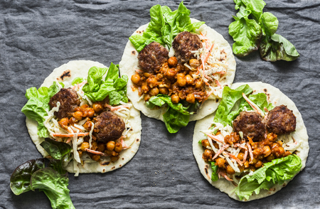 Meatballs, spicy stewed chickpeas and cabbage slaw tortilla -  delicious snack, brunch, appetizers, tapas on a gray background, top view. Flat lay, copy space