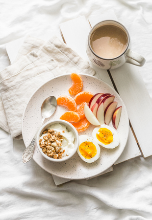 Healthy breakfast - yogurt with granola, fresh fruit apples, tangerines and coffee with milk on a light background, top view Stock Photo