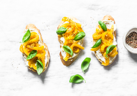 Fresh labne and baked sweet pepper bruschetta on a light background, top view. Tasty snack, tapas