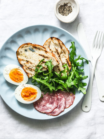 Delicious breakfast or snack - salami sausage, boiled egg, arugula, grilled bread and coffee on a light background, top view Zdjęcie Seryjne
