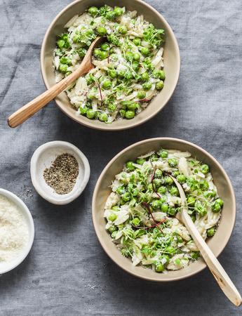 Orzo, pois verts, risotto aux herbes printanières sur fond gris, vue de dessus. Concept de cuisine végétarienne