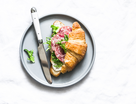 Delicious snack - salami sausage, cream cheese, green salad  croissant sandwich on a light background, top view
