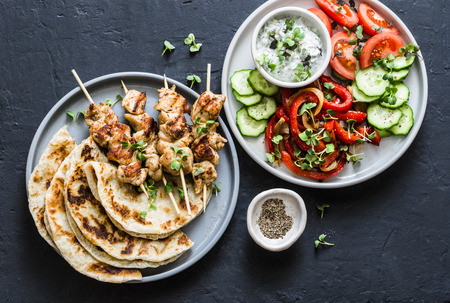 Mediterranean style lunch table - turkey skewers, flatbread, tomatoes, cucumber salad, baked sweet pepper, yogurt herb sauce  on a dark background, top view
