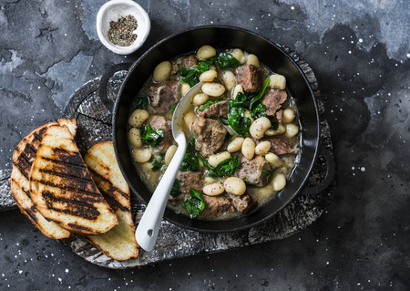 Beef, beans, spinach slow cooker stew in a pan on a wooden board on a dark background. Delicious homemade comfort food