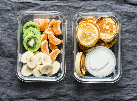 Healthy kids school, walk, picnic lunch box - pancakes with sour cream and banana, kiwi, tangerine fruit. Delicious snack on a grey background, top view