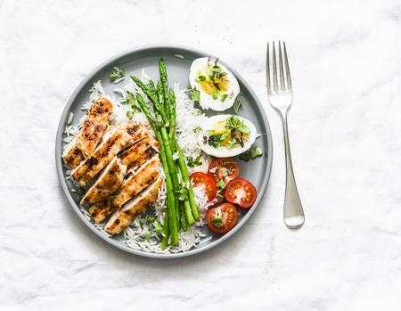 Pranzo sano equilibrato - riso, asparagi, pollo alla griglia, uova sode su uno sfondo chiaro, vista dall'alto