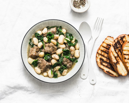 Beef, beans, spinach stew on a light background. Delicious homemade comfort food