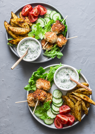 Big lunch plate - fish kebabs, roasted lemon potatoes, tzatziki sauce and fresh vegetables on a gray background, top view