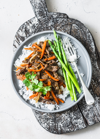 Asian style lunch - spicy fried beef, rice, asparagus on light background, top view