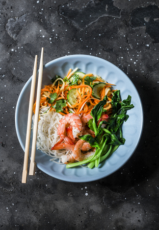 Asian food bowl - rice noodles, shrimp, cabbage bok choy and quickly pickled vegetables carrots, cucumbers, daikon salad on a dark background, top view Imagens
