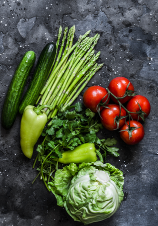 Fresh vegetables background - tomatoes, asparagus, cabbage, cucumbers, peppers and cilantro on a dark background, top view. Healthy food diet concept. Flat lay Imagens