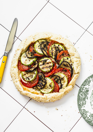 Grilled vegetables and mozzarella cheese puff pastry galette. Grilled eggplant, zucchini, tomatoes, cheese, thyme pie on a light background, top view