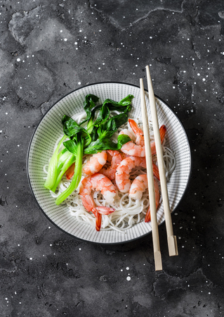 Rice noodles with shrimp and bok choy cabbage on a dark background, top view Imagens