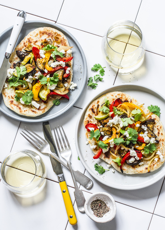 Grilled vegetables tortilla and white wine - delicious vegetarian lunch on a light background, top view. Mediterranean style food
