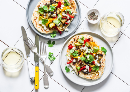 Grilled vegetables flatbread and white wine - delicious vegetarian lunch on a light background, top view. Mediterranean style food Imagens