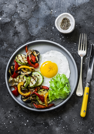 Delicious breakfast or snack - grilled vegetables and fried egg on a dark background, top view Imagens