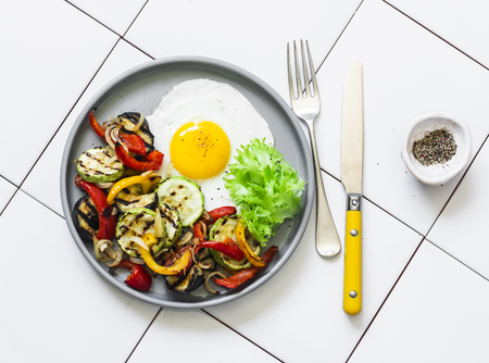 Delicious breakfast or snack - grilled vegetables and fried egg on a light background, top view Imagens