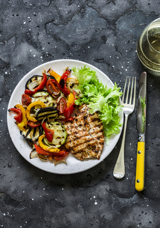 Grilled vegetables, chicken breast and a glass of white wine - delicious healthy diet lunch on a dark background, top view Imagens
