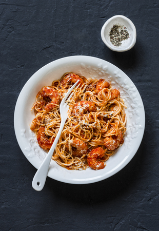 Shrimp tomato sauce spaghetti on a dark background, top view Imagens