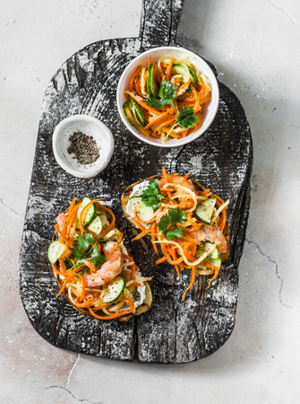 Shrimp banh mi sandwiches on rustic wooden cutting board on a light background, top view. Grilled bread quickly pickled vegetables and prawns sandwiches Imagens