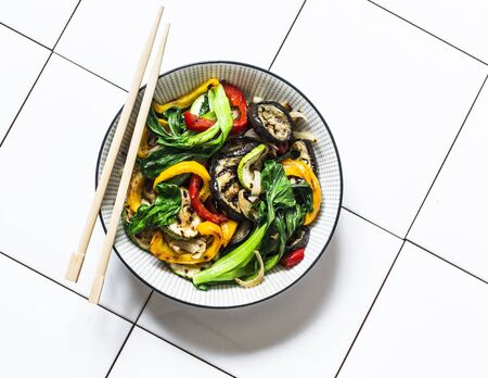 Stir fry vegetables in asian style. Quickly roasted wok vegetables - bok choy, eggplant, bell pepper, zucchini on a light background, top view
