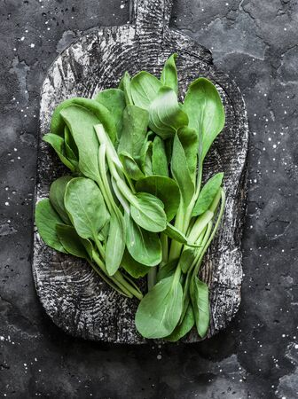 Baby Bok Choy cabbage on rustic wood cutting board on dark background. Healthy food ingredient