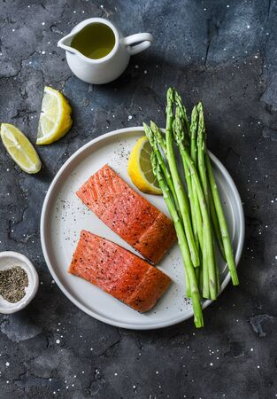 Healthy food ingredients - red fish salmon and fresh green asparagus on a dark background, top view