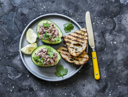 Tuna stuffed avocado - delicious healthy food on a dark background, top view Imagens