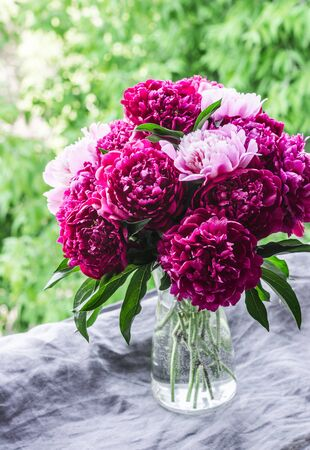 Beautiful bouquet of peonies on the window overlooking the garden - a cozy home still life. Natural beauty concept Imagens