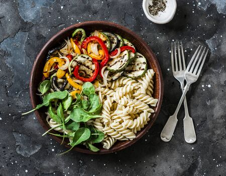 Roasted vegetables and fusilli pasta antipasti salad on dark background, top view