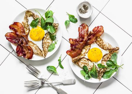 Stuffed egg crepes with bacon and arugula - delicious nutritious brunch on a light background, top view. Flat lay Imagens