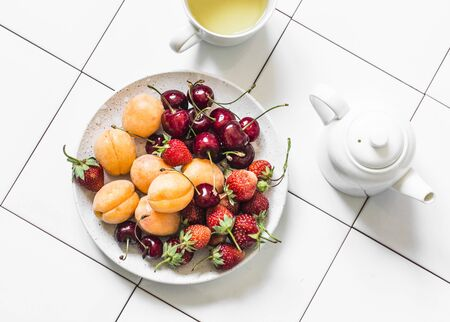 Delicious healthy dessert - fresh ripe fruits and berries strawberries, apricots, cherries and green tea on a light background, top view Stock Photo