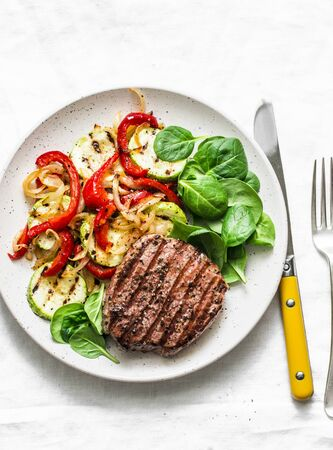 Grilled beef cutlet and vegetables - delicious healthy balanced lunch on a light background, top view