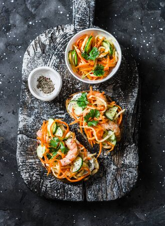 Shrimp banh mi sandwiches on rustic wooden cutting board on a dark background, top view. Grilled bread quickly pickled vegetables and prawns sandwiches