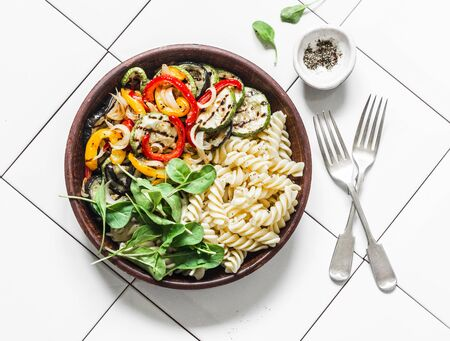 Roasted vegetables and fusilli pasta antipasti salad on light background, top view Imagens