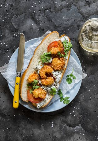 Po boy sandwich with crispy cornmeal shrimp, tomatoes, cilantro and mayo herbs sauce on dark background, top view Imagens