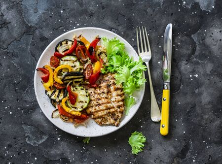 Grilled vegetables, chicken breast - delicious healthy diet lunch on a dark background, top view