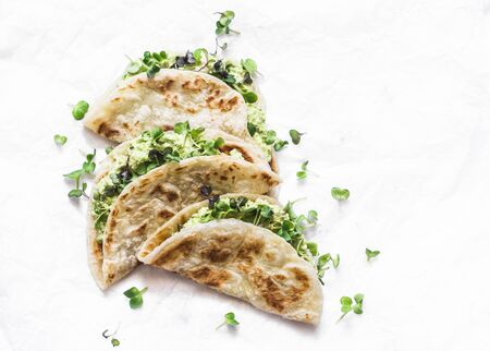Avocado micro greens quesadilla on a light background, top view
