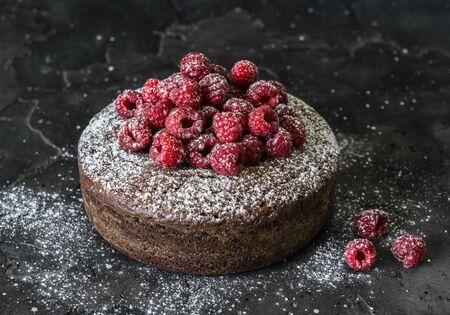 Chocolate nut cake with fresh raspberry on dark background. Delicious dessert