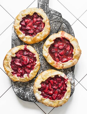 Strawberry pie on a wooden rustic board on a light background