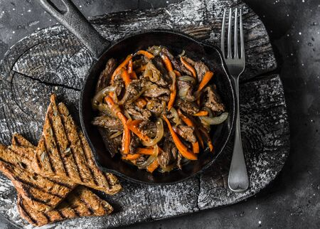 Slow cooker braised beef with onions and carrots in a pan on a dark background, top view