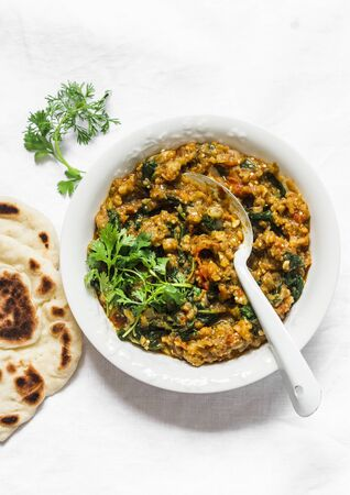 Aubergine spinach vegetarian curry with naan flatbread on a light background, top view. Indian cuisine